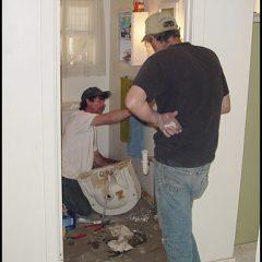Crew installing new plumbing for bathroom sink.